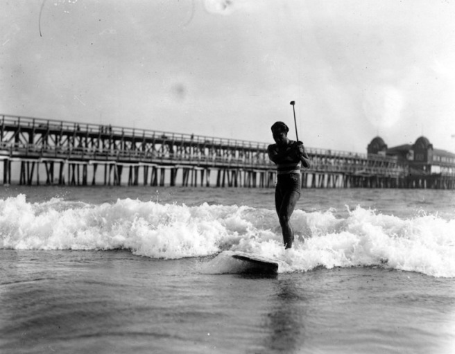 Duke Kahanamoku practices his golf swing will riding his surfboard towards shore. A long pier stretches outwards in the background, c. 1925 (Image source: Los Angeles Public Library Images)