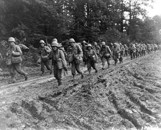 The 442nd Regimental Combat Team hiking up a muddy French road in the Chambois Sector, France, in late 1944.
