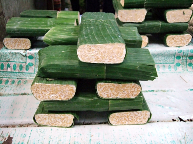 Fresh tempeh at the market, Jakarta, Indonesia – traditionally, tempeh is wrapped in banana leaves. (Image source: Sakurai Midori)